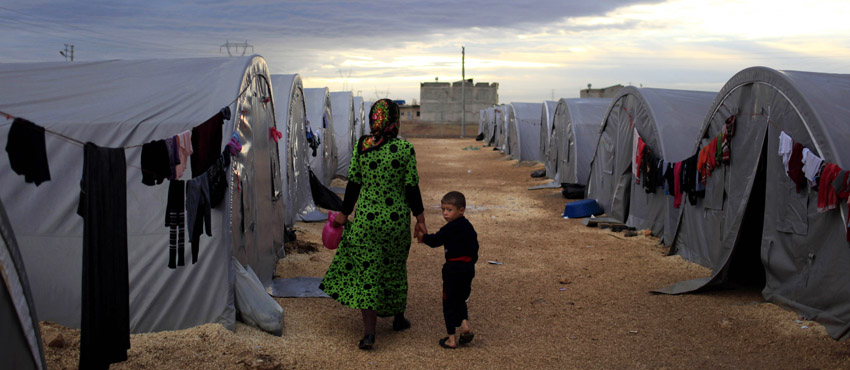 SANLIURFA, TURKEY -  OCTOBER 19:  (TURKEY OUT)   A Kurdish refugee mother and son from the Syrian town of Kobani walk beside their tent in a camp in the southeastern town of Suruc on the Turkish-Syrian border on October 19, 2014 in Sanliurfa, Turkey.  Kurdish fighters in Syrian city of Kobani have pushed back Islamic State militants in a number of locations as U.S. air strikes on ISIS positions continue in and around the city. In the past month more than 200,000 people from Kobani have fled into Turkey. (Photo by Gokhan Sahin/Getty Images)